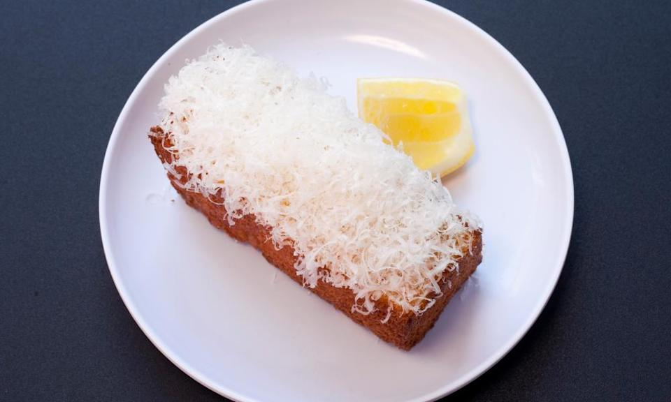 A round white plate with a rectangular 'cake' topped with white shredding and a slice of lemon next to it