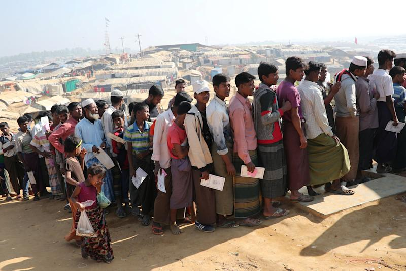 Rohingya refugees stand in a queue to collect aid supplies in Kutupalong refugee camp in Cox's Bazar, Bangladesh, January 21, 2018.