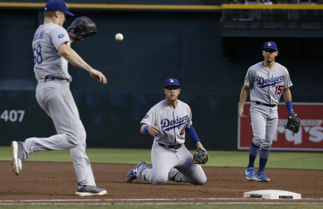Los Angeles Dodgers first baseman Matt Beaty, middle, tosses the ball to Dodgers starting pitcher Ross Stripling (68) to get Arizona Diamondbacks' Eduardo Escobar out at first base as Dodgers' Austin Barnes (15) looks on during the third inning of a baseball game, Tuesday, June 25, 2019, in Phoenix. (AP Photo/Ross D. Franklin)