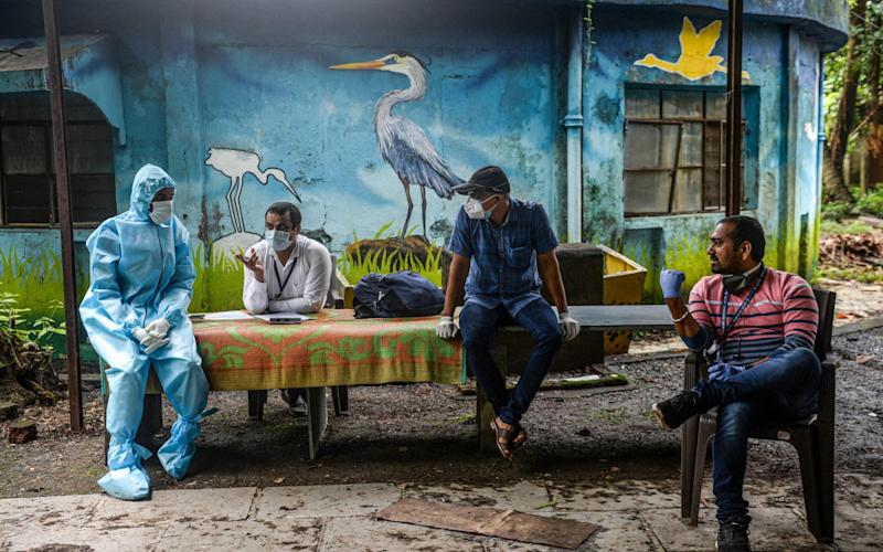 Health workers and civic staff wait for students at the Children Aid Society premises during a medical screening for coronavirus in Mumbai - INDRANIL MUKHERJEE/AFP