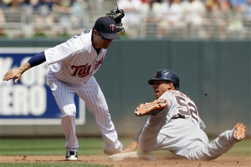 Detroit Tigers' Quintin Berry (52) looks back for the call as Minnesota Twins shortstop Jamey Carroll (8) makes the tag during the second inning in a baseball game, Sunday, May 27, 2012, in Minneapolis. Berry was safe on the play. (AP Photo/Paul Battaglia)