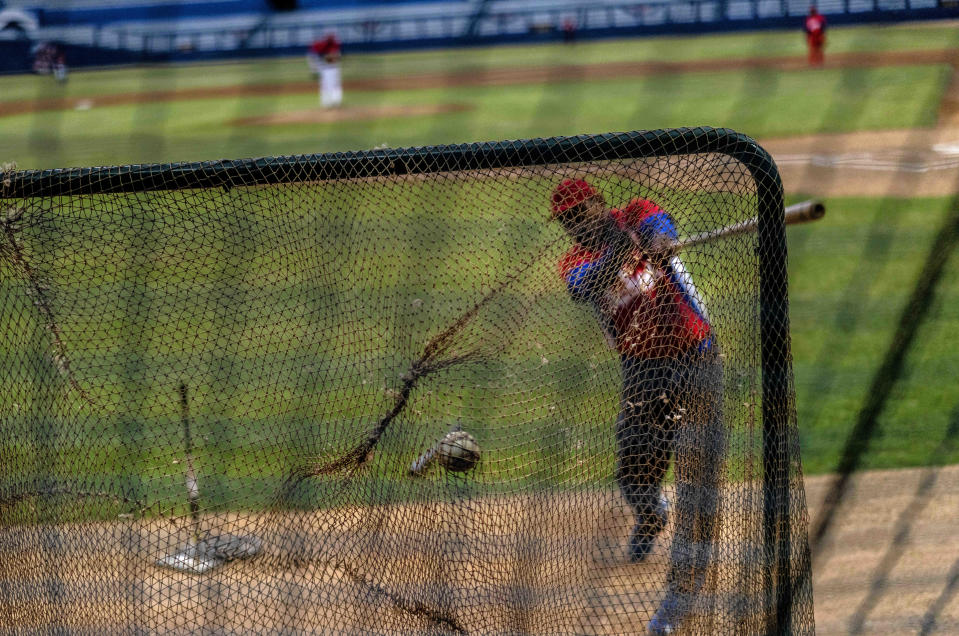 A Cuban baseball player hits the ball during a training session at the Estadio Latinoamericano in Havana, Cuba, Tuesday, May 18, 2021. A little over a week after the start of the Las Americas Baseball Pre-Olympic in Florida, the Cuban team does not have visas to travel to the United States. (AP Photo / Ramon Espinosa)