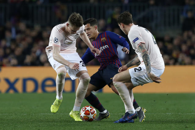 Barcelona forward Philippe Coutinho, center, fights for the ball with Manchester United's Scott McTominay, left, and Manchester United's Victor Lindelof during the Champions League quarterfinal, second leg, soccer match between FC Barcelona and Manchester United at the Camp Nou stadium in Barcelona, Spain, Tuesday, April 16, 2019. (AP Photo/Joan Monfort)