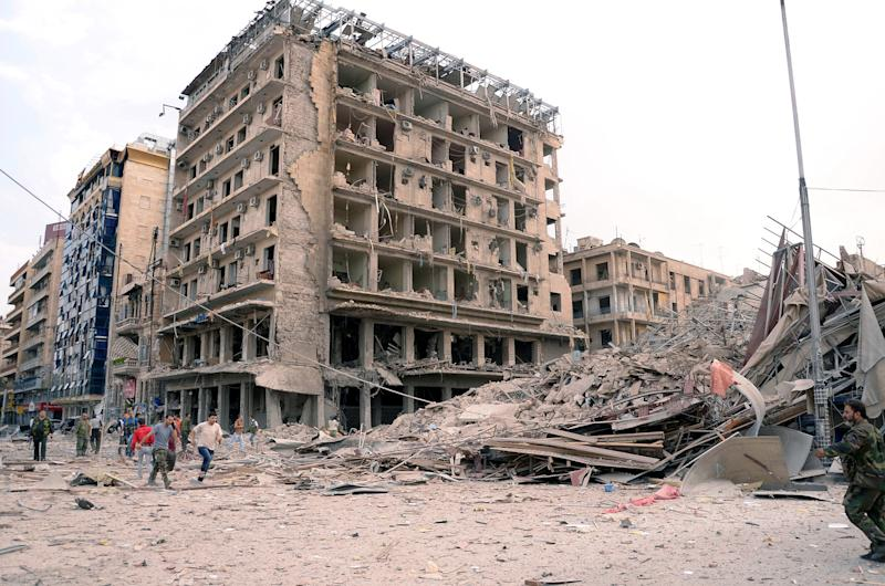 In this photo released by the Syrian official news agency SANA, Syrian security officers run at the scene in front of destroyed buildings where triple bombs exploded at the Saadallah al-Jabri square, in Aleppo city, Syria, Wednesday, Oct. 3, 2012. Three powerful explosions rocked the main square in a government-controlled central district of Aleppo on Wednesday, the Syrian state-run TV said. Activists reported multiple casualties and heavy material damage. (AP Photo/SANA)