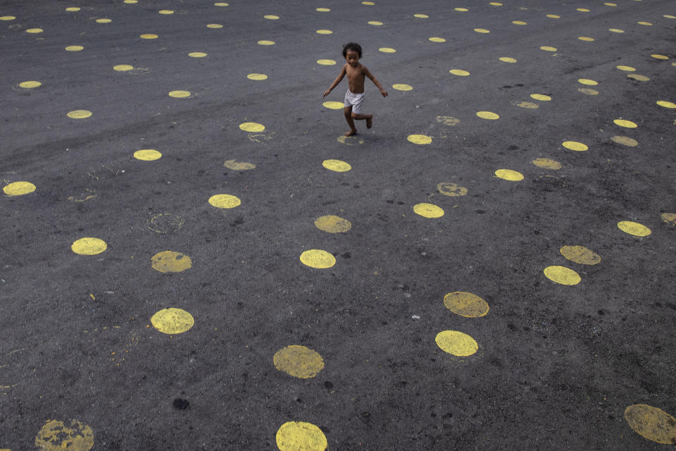 A child runs over social distancing markers on the road as part of preparations for masses a day before the Feast of Santo Niño (Baby Jesus) on January 16, 2021 in Manila, Philippines. (Photo: Ezra Acayan/Getty Images)