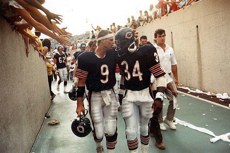 Walter Payton (34) leaves the field with Jim McMahon (9) after the Bears beat Tampa Bay in the 1985 season opener. (Charles Cherney/Chicago Tribune/Tribune News Service via Getty Images)