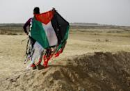 A Palestinian youth holds a kite in the colours of his national flag near the Gaza-Israel border on April 20, 2018