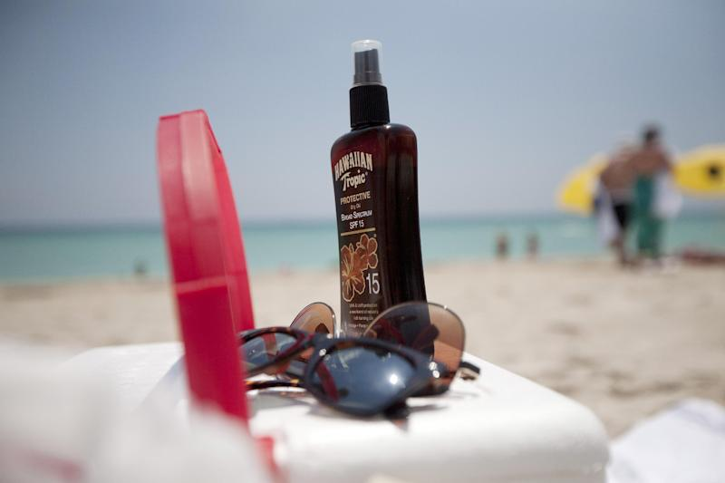 This Wednesday, May 9, 2012 file photo shows a bottle of sun tan lotion and sunglasses on top of a cooler carried onto Miami Beach, Fla. by tourists. Sunscreen confusion won't be over before summer after all. The government is bowing to industry requests for more time to make clear how much protection their lotions really offer. (AP Photo/J Pat Carter, File)