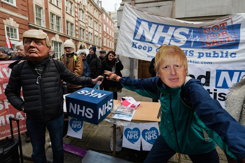 Demonstrators wearing masks of Donald Trump and Boris Johnson take part in a protest for keeping the National Health Service (NHS) publicly owned outside the Conservative Party HQ before marching to Downing Street with a petition, signed by over 1 million people, demanding that the NHS is excluded from any post-Brexit trade deals on December 09, 2019 in London, England. Photo: Getty