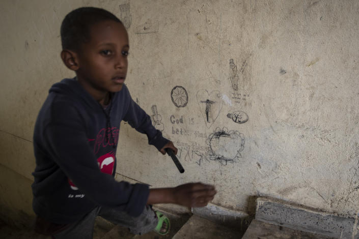"""A displaced Tigrayan boy runs up stairs past graffiti reading """"God is better than any thing"""" at the Hadnet General Secondary School which has become a makeshift home to thousands displaced by the conflict, in Mekele, in the Tigray region of northern Ethiopia Wednesday, May 5, 2021. The Tigray conflict has displaced more than 1 million people, the International Organization for Migration reported in April, and the numbers continue to rise. (AP Photo/Ben Curtis)"""