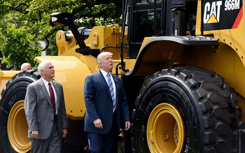President Donald Trump and Vice President Mike Pence examine an iconic Yellow Iron from Caterpillar Inc. - Credit: AFP