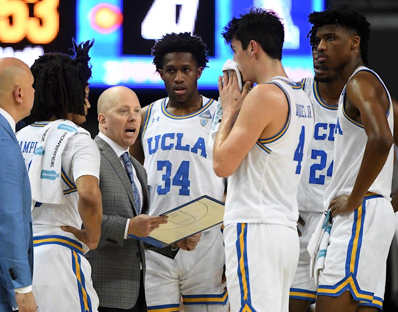 Tyger Campbell (10), David Singleton (34), Jaime Jaquez Jr. (4), Jalen Hill (24) and Chris Smith (5) of the UCLA Bruins listen as head coach Mick Cronin talks during a timeout on Feb. 29. (Kamin-Oncea/Getty Images)