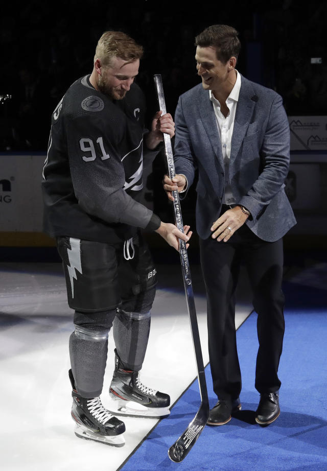 Former Tampa Bay Lightning player Vincent Lecavalier, right, presents Tampa Bay Lightning's Steven Stamkos (91) with a silver stick before an NHL hockey game against the Washington Capitals Saturday, March 30, 2019, in Tampa, Fla. Stamkos became the Lightning's all-time goal scoring leader. (AP Photo/Chris O'Meara)