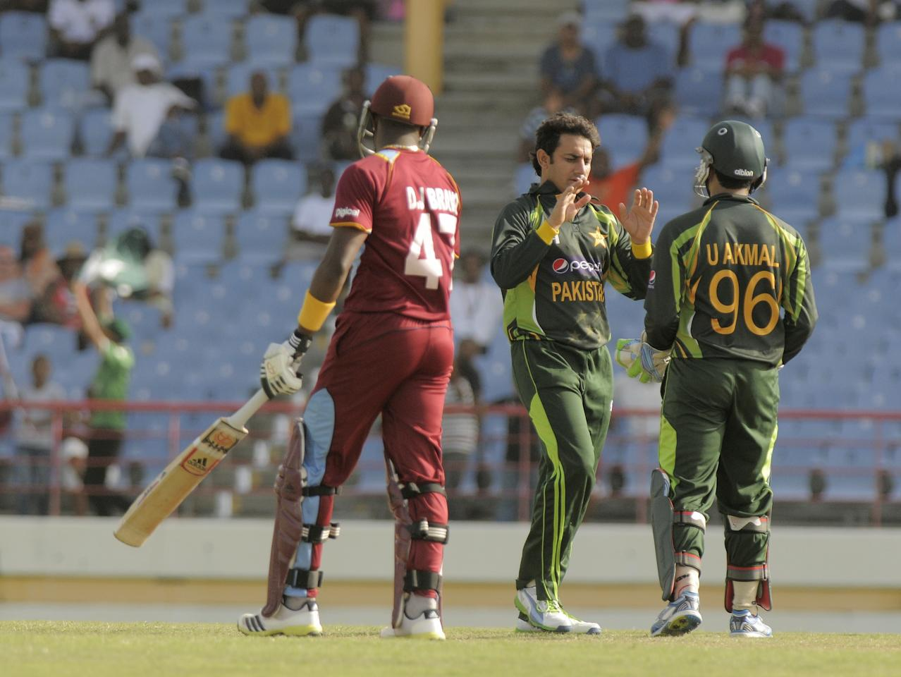 Pakistan bowler Saeed Ajmal (C) celebrates with Umar Akmal (R) the dismissal of West Indies batsman DJ Bravo (L) bowled for 17 runs, July 19, 2013 during the 3rd ODI West Indies v Pakistan at Beausejour Cricket Ground, St. Lucia. Score, Pakistan 229/6, West Indies 229/9, match tied.       AFP PHOTO / Randy Brooks        (Photo credit should read RANDY BROOKS/AFP/Getty Images)