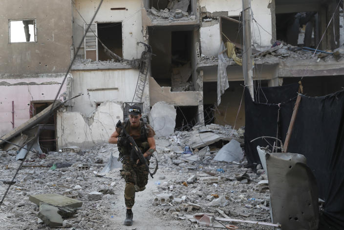 FILE - In this July 27, 2017 file photo, a U.S.-backed Syrian Democratic Forces fighter runs in front of a damaged building as he crosses a street on the front line, in Raqqa, Syria. Syrian activists said Friday, Dec. 14, 2018 that U.S.-backed, Kurdish-led fighters have captured the last town held by the Islamic State group, in the militants' single remaining enclave in eastern Syria. (AP Photo/Hussein Malla, File)