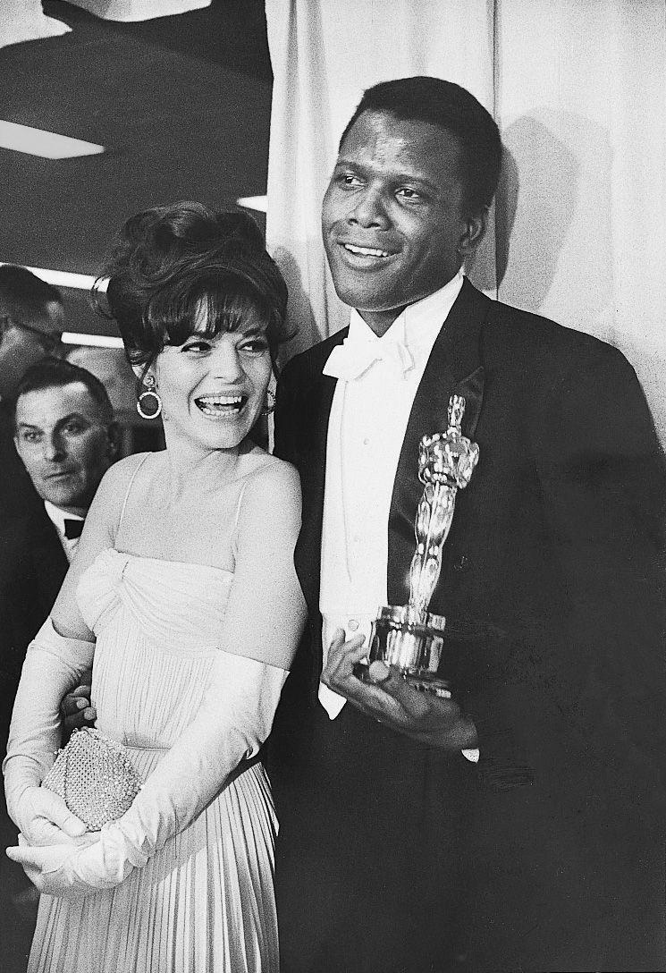 <p>Anne killed it in this simple pleated dress paired with opera-length gloves and a sparkly evening bag. The Best Actress winner posed with Sidney Poitier, who won Best Actor that same evening.</p>
