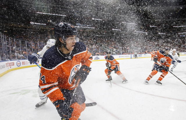 Edmonton Oilers' Ethan Bear (74) is surrounded by ice as he looks for the pass against the Toronto Maple Leafs during third period NHL action in Edmonton, Alberta, on Saturday, Dec. 14, 2019. (Jason Franson/The Canadian Press via AP)