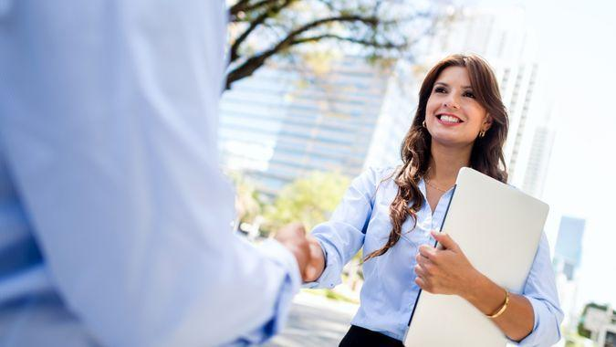 Business woman shaking hands with a client - outdoors.