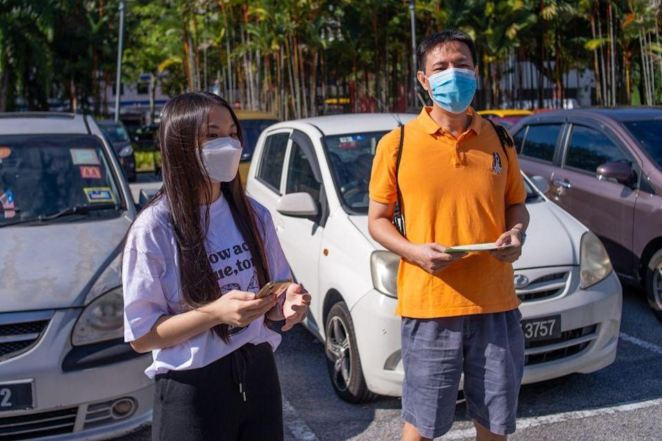 Nigel (right) and Corrine Chong speak to reporters outside the Axiata Arena Covid-19 vaccination centre in Bukit Jalil September 23, 2021. — Picture by Shafwan Zaidon