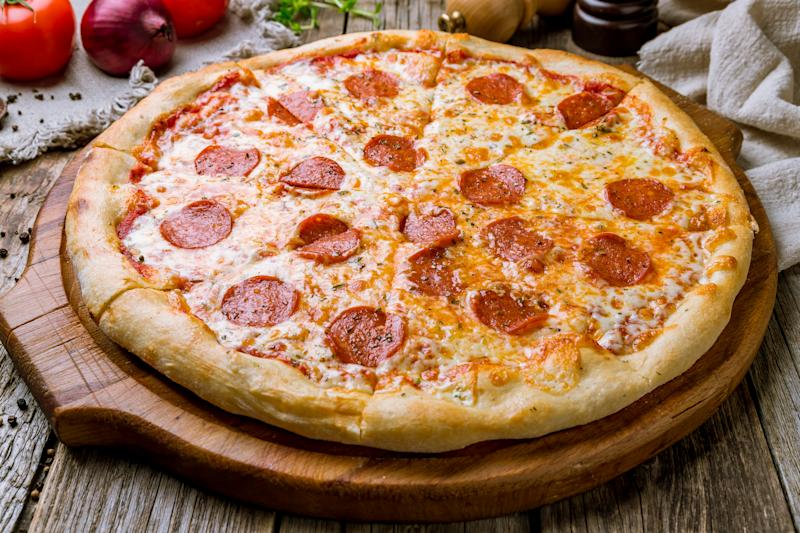 Pepperoni pizza on board on wooden background