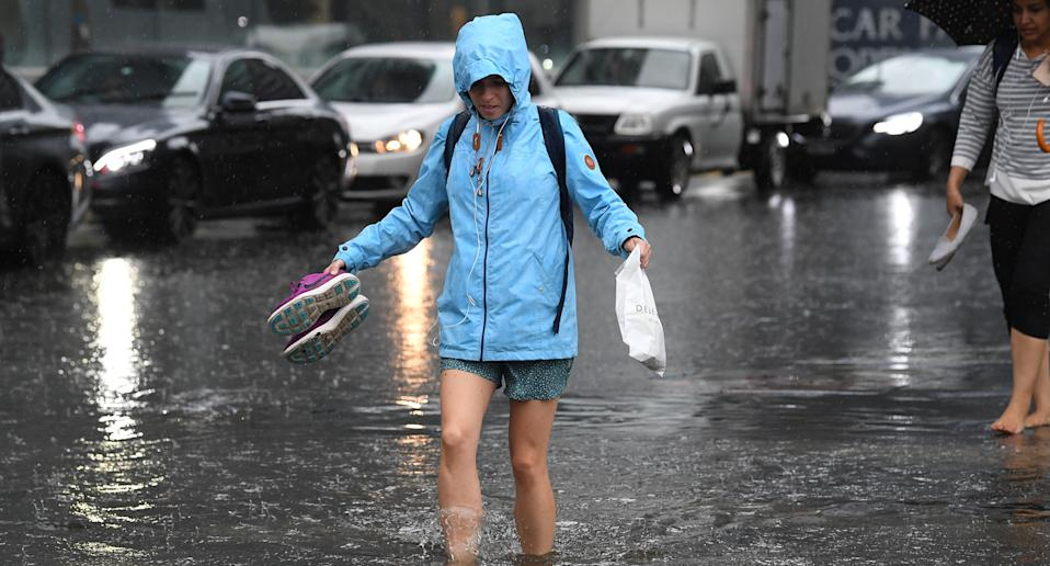 Redestrians walk through flood waters at the corner of Clarendon and Cecil Street in South Melbourne, December 13, 2018