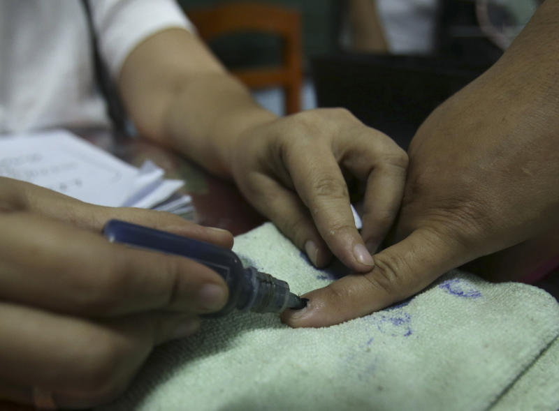 An election worker places ink on the finger of a voter at a classroom used as a voting precinct during mid-term elections in Manila, Philippines on Monday, May 13, 2013. The country is electing local officials from senators to congressmen and down to municipal mayors during Monday's mid-term elections. (AP Photo/Aaron Favila)