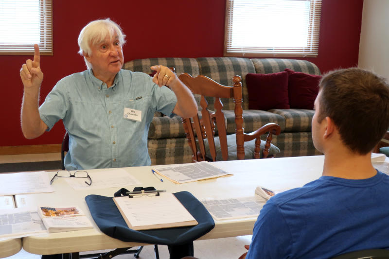 Democratic organizer Bill Chandler talks with a volunteer about how to speak with voters when distributing campaign material in Wisconsin on Saturday, Sept. 21, 2019, in Whitewater, Wis. Chandler is executing the Democratic strategy to win back Wisconsin _ a block-by-block rebuilding of the infrastructure they let crumble ahead of the last presidential election. Many Democrats in Wisconsin, and across the Rust Belt states that President Donald Trump flipped Republican in 2016, believe their weak neighborhood network contributed to their defeat.  (AP Photo/Scott Bauer)