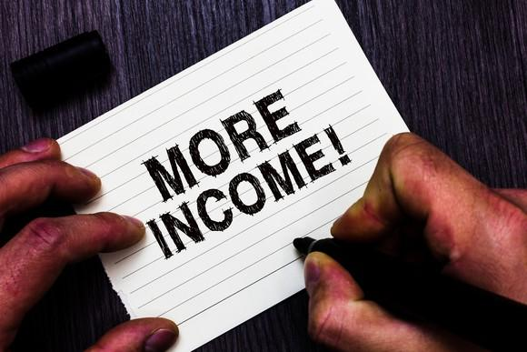 """Two hands writing """"MORE INCOME!"""" on an index card."""