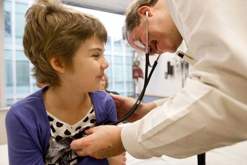 In this October 2012 photo provided by The Children's Hospital of Philadelphia, Emily Whitehead is checked by pediatric oncologist, Dr. Stephan A. Grupp, at the hospital. In early 2012, she was the first child given gene therapy for acute lymphocytic leukemia and shows no sign of cancer today, nearly 21 months after. (AP Photo/The Children's Hospital of Philadelphia, Ed Cunicelli)