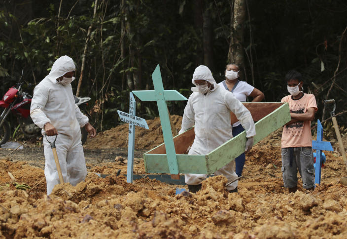 In this April 16, 2020 photo, funeral workers in protective gear prepare the grave of a woman who is suspected to have died of COVID-19 disease, at the Nossa Senhora Aparecida cemetery, in Manaus, Amazonas state, Brazil. Gravediggers buried 60 people that day, about triple the pre-virus average, according to a cemetery official. (AP Photo/Edmar Barros)