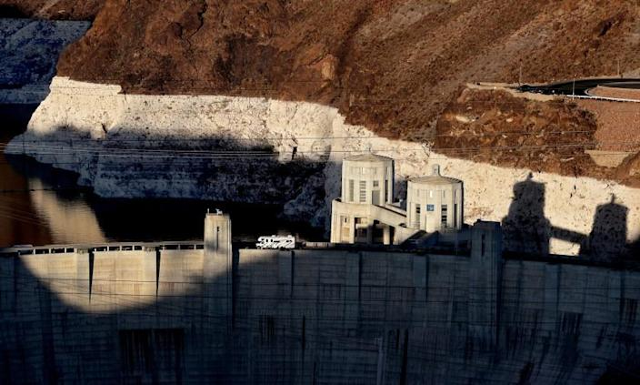 """LAKE MEAD, NEV. - JUNE 11, 2021. A motorhome travels across the Hoover Dam near Boulder City, Nev. A white """"bathtub ring"""" above the dam hows how far below capacity Lake Mead - the nation's largest reservoir - currently is. Water levels at Lake Mead have hit their lowest points in history amid an ongoing megadrought, creating uncertainty about the water supply for millions of people in the western United States. (Luis Sinco / Los Angeles Times)"""