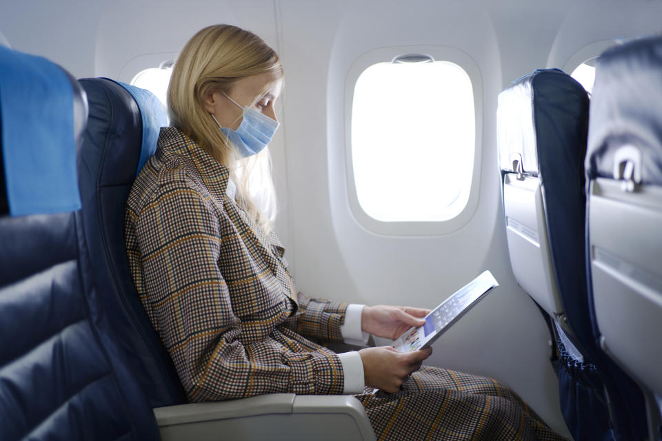 Portrait of young beautiful woman with long blond hair wearing mask inside airplane while reading safety instructions.
