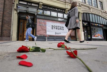 Flowers lie on the sidewalk at the site of the first explosion as people walk along Boylston Street in Boston