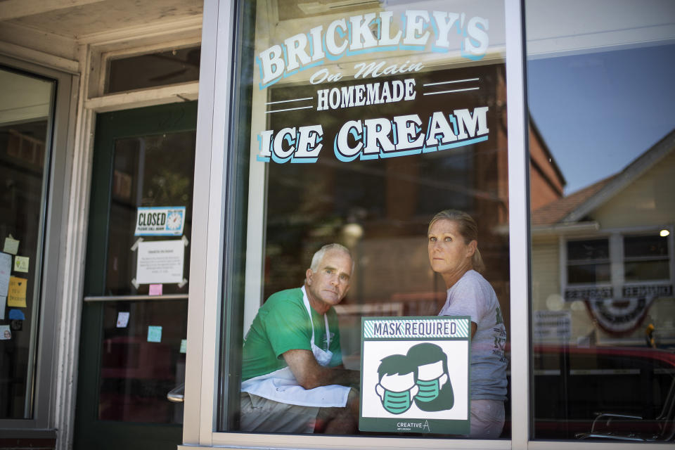 """Steve, left, and Chris Brophy, husband and wife owners of Brickley's Ice Cream, look out from the shop they closed after teenage workers were harassed by customers who refused to wear a mask or socially distance, in Wakefield, R.I., Wednesday, July 29, 2020. """"Some of them don't believe it's real (COVID-19) and some don't think it's a big deal, I do,"""" Steve Brophy said, adding that he would rather close than put young workers and customers at risk of harassment, and the virus. """"It's like it's OK to be a jerk in this environment."""" (AP Photo/David Goldman)"""