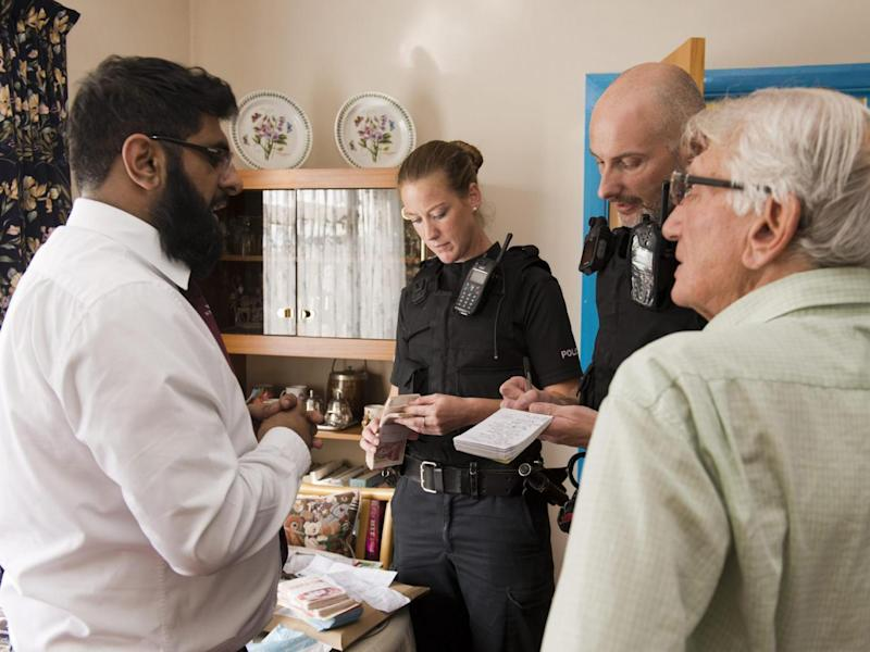 Izy Rashid (left) talks to the police while an officer checks the money he had just handed back to Mr Stone