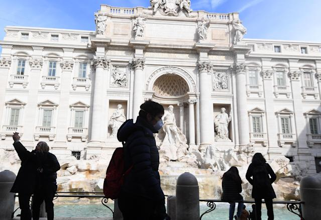 A man with a face mask visits the Fontana di Trevi in Rome (Getty)
