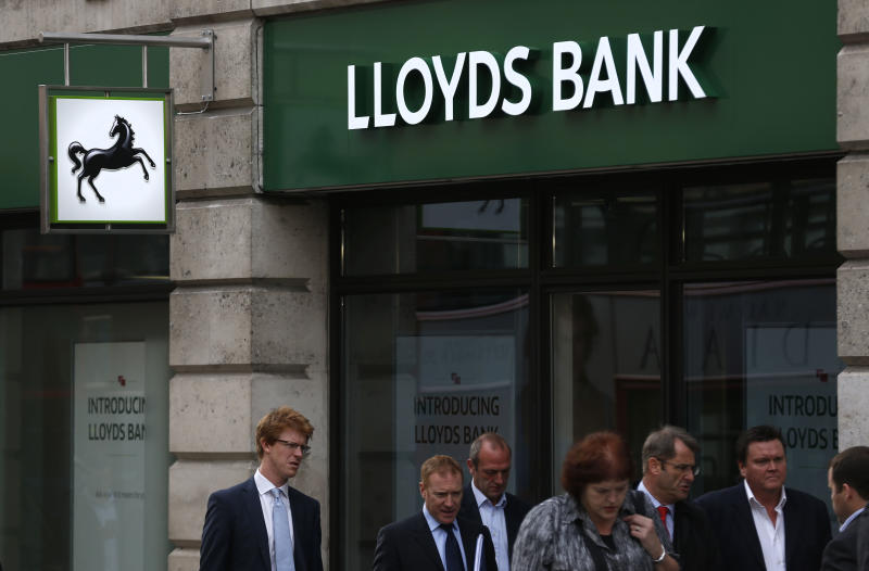 People walk by a branch of Lloyds Bank in the City of London, Tuesday, Sept. 17, 2013. Britain's investment authority says it has begun the privatization of the Lloyds banking group, one of several UK banks bailed out at the height of world financial crisis. Financial Investments, the arm of the British government which manages the country's stakes in Lloyds and the Royal Bank of Scotland, said it was selling 6 percent of Lloyds shares. (AP Photo/Sang Tan)