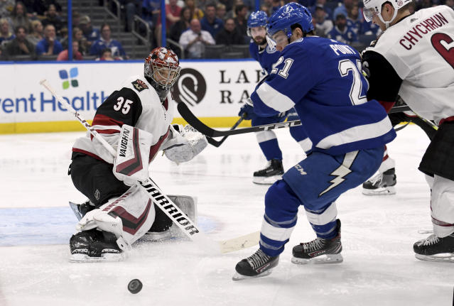 Arizona Coyotes goaltender Darcy Kuemper (35) deflects a shot as Tampa Bay Lightning center Brayden Point (21) looks for the rebound during the second period of an NHL hockey game Monday, March 18, 2019, in Tampa, Fla. (AP Photo/Jason Behnken)