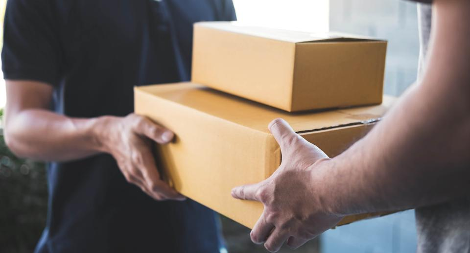 Delivery mail man giving parcel box to recipient, Young owner accepting of cardboard boxes package from post shipment, Home courier and delivery service mind concept. Source: Getty Images