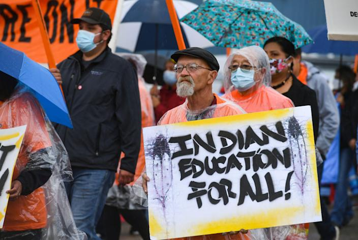 """Gaylord Atkins holds a sign that reads """"Indian education for all!"""" during a demonstration through the streets of Pierre after the final draft of the state's proposed social studies standards left out multiple specific references to the Oceti Sakowin on Monday, September 13, 2021."""
