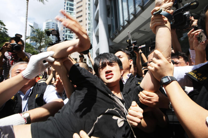 Bailiffs carry a protester away from a public space underneath HSBC's Asian headquarters in Hong Kong, Tuesday, Sept. 11, 2012. Hong Kong's Occupy activists were locked in a standoff Tuesday with bailiffs trying to evict them from the site. (AP Photo/Kin Cheung)