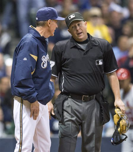 Milwaukee Brewers manager Ron Roenicke talks with home plate umpire Todd Tichenor, who ruled that St. Louis Cardinals' Matt Holliday was safe at home during the third inning of a baseball game Thursday, May 2, 2013, in Milwaukee. (AP Photo/Tom Lynn)