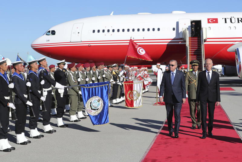 Turkey's President Recep Tayyip Erdogan, left, Tunisian President Kais Saied, right, inspect a military honour guard at the airport, in Tunis, Tunisia, Wednesday, Dec. 25, 2019. Erdogan with top Turkish officials is on an unannounced visit to Tunisia to meet Saied. (Turkish Presidency via AP, Pool)