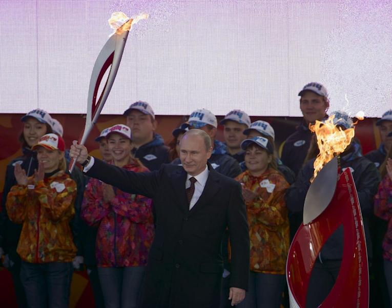 Russian President Vladimir Putin, centre, smiles as he lights the Olympic flame with a torch, at the Red Square, Moscow, Sunday, Oct. 6, 2013. Russian President Vladimir Putin ceremoniously lit the Olympic flame on Red Square on Sunday, but the four-month relay to Sochi for the Winter Games got off to a rocky start when one of the torches went out. The Olympic flame, which was lit a week ago in Greece and flown to Moscow earlier Sunday, kept burning in a cauldron on Red Square. (AP Photo/Ivan Sekretarev)