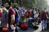 Kashmiris, mostly students, stranded for weeks wait to board buses to a special train home during a lockdown to curb the spread of new coronavirus, in Bangalore, India, Sunday, May 10, 2020. India's lockdown entered a sixth week on Sunday, though some restrictions have been eased for self-employed people unable to access government support to return to work. (Aijaz Rahi)
