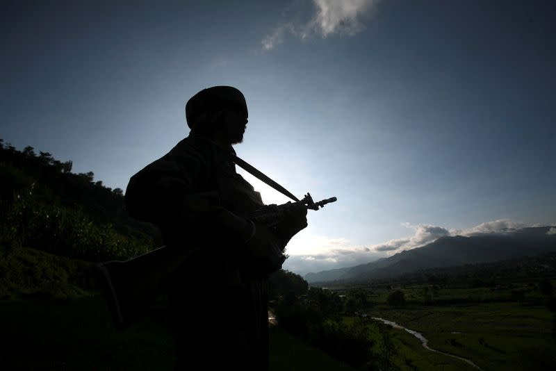 FILE PHOTO: An Indian army soldier stands guard while patrolling near the Line of Control, a ceasefire line dividing Kashmir between India and Pakistan, in Poonch