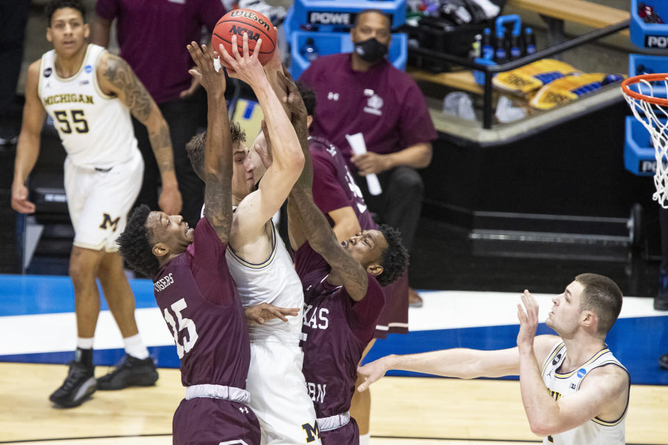 Michigan's Franz Wagner, center, goes up for a shot between Texas Southern's Justin Hopkins, left, and Joirdon Karl Nicholas, next to Michigan's Hunter Dickinson, right, during the first half of a First Round game in the NCAA men's college basketball tournament, Saturday, March 20, 2021, at Mackey Arena in West Lafayette, Ind. (AP Photo/Robert Franklin)