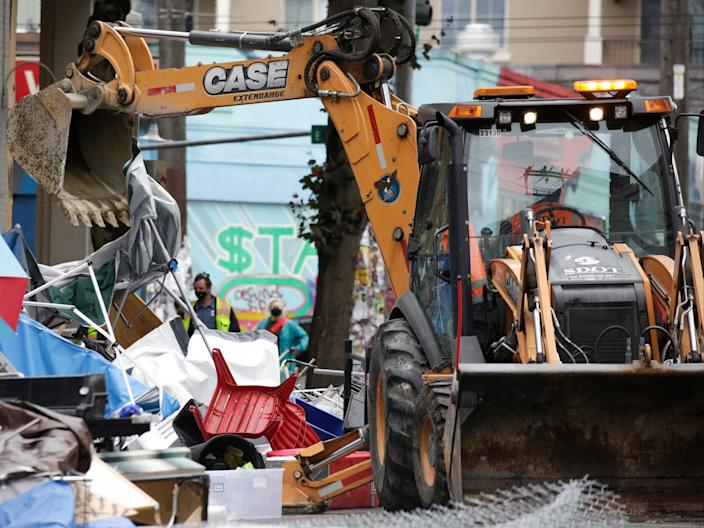 Workers use a bulldozer to remove remaining items from an encampment outside the Seattle Police Department's East Precinct after police cleared the Capitol Hill Occupied Protest (CHOP) in Seattle, Washington on 1 July, 2020 (AFP via Getty Images)