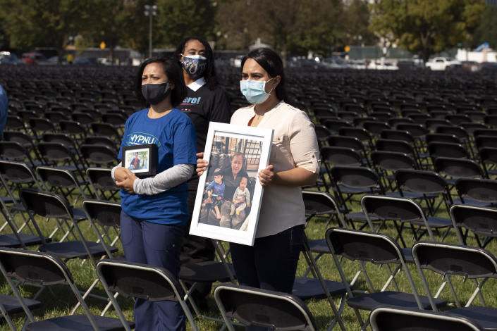 Liza Billing, left, and Naeha Quasba hold photographs of their loved ones, who lost their life due the COVID-19, during the National COVID-19 Remembrance, at The Ellipse outside of the White House, Sunday, Oct. 4, 2020, in Washington. (AP Photo/Jose Luis Magana)