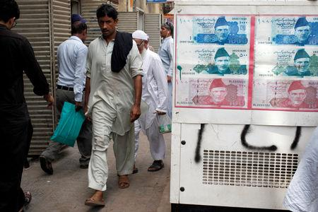 FILE PHOTO: Passersby walk past an advertisement board with photos of Pakistani rupee at a money exchange along a sidewalk in Karachi